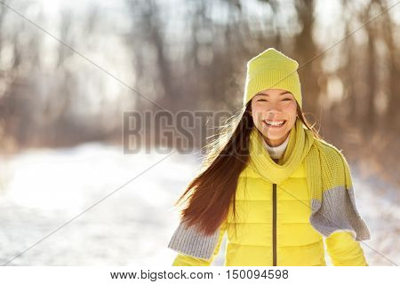 Happy cute winter girl smiling in snow forest. Portrait of Asian woman happy playful outdoors with healthy smile on sunny wintertime day wearing yellow outerwear beanie knit hat and scarf.