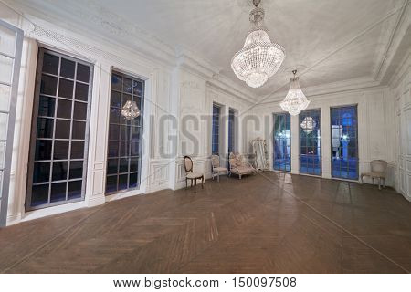 MOSCOW, RUSSIA - JUN 10, 2016: Room with high ceiling, chandeliers, parquet-flooring, old-fashioned furniture. Interior of Royal Studio.