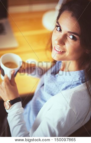 Portrait of relaxed young woman sitting at her desk holding cup of coffee
