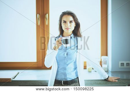 Happy woman drinking tea in the kitchen at home