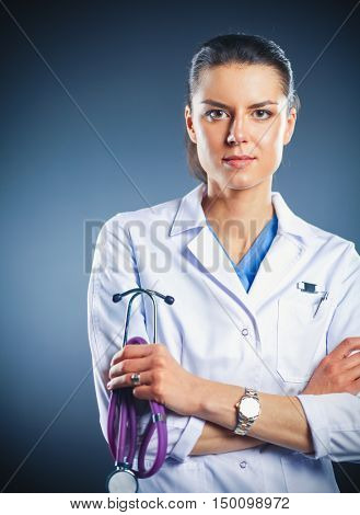 Portrait of young female doctor holding a stethoscope, isolated on black background