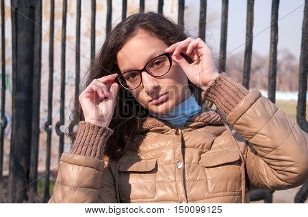 Girl holds hands glasses and tilted her head to one side