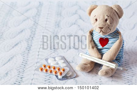 children's soft toy teddy bear with pills takes the temperature of a mercury glass thermometer. child's disease.