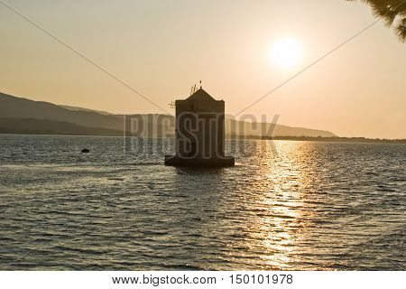 Water mill on the sea at sunset
