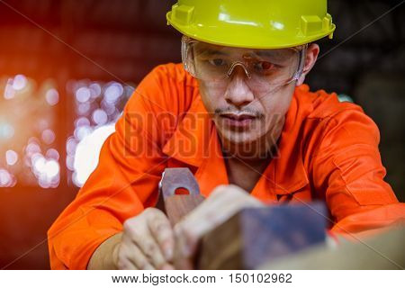 Asian young man carpenter working with plane on wooden background