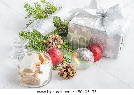 Christmas gift box in silver wrapping paper over a white fluffy background. A jar full of star cookies and christmas decoration.
