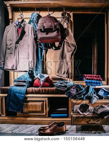 Male fashion stylish casual clothes in home wardrobe. Jacket, jeans, shirt, jumper, shoes, backpack