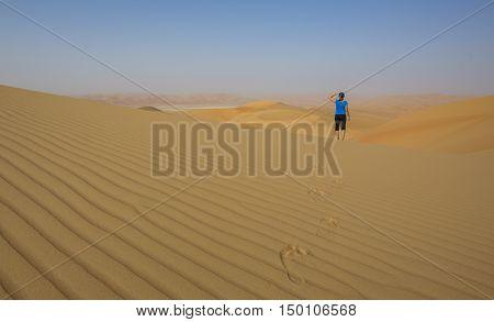 Woman walking in Liwa desert, part of Empty Quarter desert