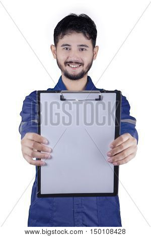 Male Arabian mechanic showing empty clipboard while wearing uniform in the studio isolated on white background