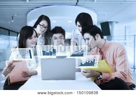 Group of young Asian businesspeople discussing in the office room with virtual financial graph on the laptop