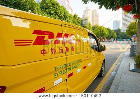 SHENZHEN, CHINA - FEBRUARY 05, 2016: a DHL car in the street. DHL Express is a division of the German logistics company Deutsche Post DHL providing international express mail services.