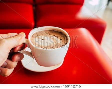 Hand holding white coffee cup on red table.
