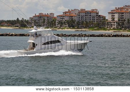 Upscale  sport fishing boat cruising past luxury condominium buildings on a private island in Mimi,Florida.