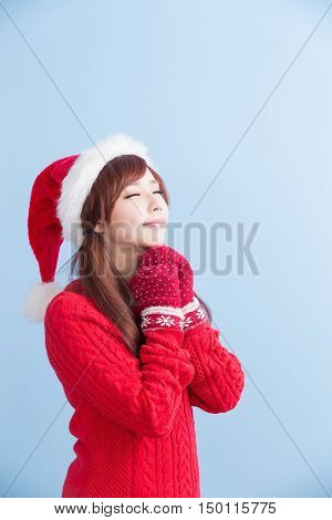 christmas beauty girl make a wish with red hat and cloth isolated on blue background asian