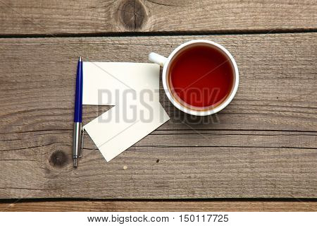 Blank business cards with pen and tea cup on wooden office table.