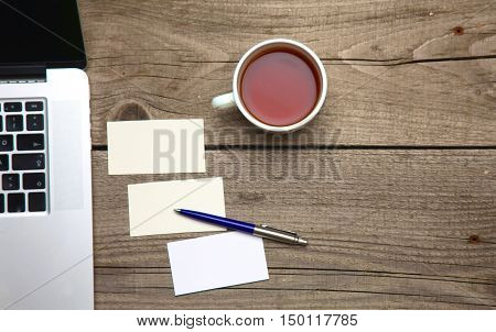 Blank business cards with pen, laptop and tea cup on wooden office table.