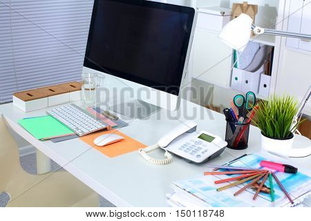 Office working desk with computer and paperwork.