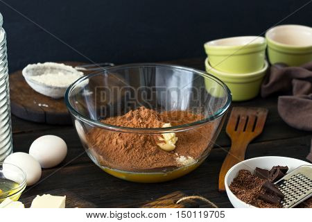Different ingredients for preparing delicious chocolate dessert on dark wooden table close up