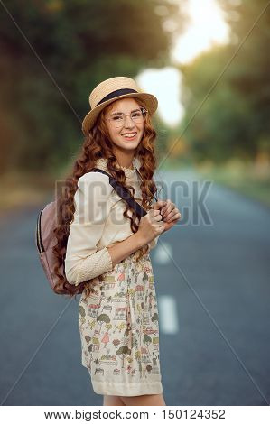 Young girl traveler enjoy the travel on foot. Portrait of happy smilingwoman walking with hat and backpack on the road and looking at camera. Adventure is coming concept