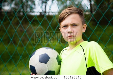 Boy with a ball playing football on stadium