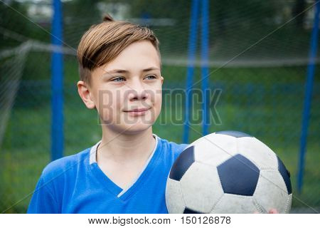 Smiling boy with a ball at stadium