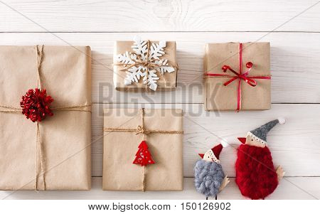 Christmas background with copy space. Top view of gift boxes and funny birds toys. Presents in craft paper with red ribbon bows on white wood. Celebration of winter holidays concept