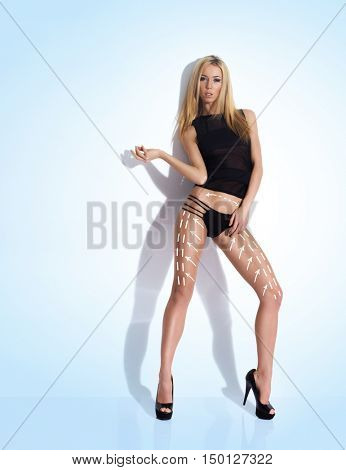 Seductive woman with arrows on body in underwear. Liposction concept.