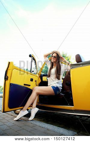 Traveler woman resting on a car wheel during a stop on road trip vacation travel. Young woman relaxing in the car with sunlit backlit road in background