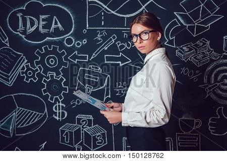 Portrait of a business woman with glasses on a background with business figures