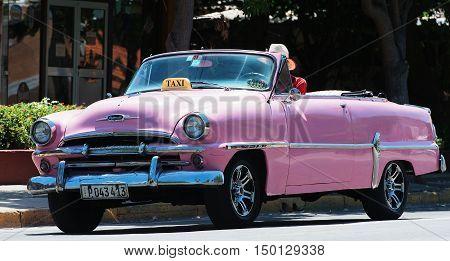 Varadero, Cuba - September 11, 2016:  pink American Cabriolet Classic Car Dirves in Varadero City, Cuba