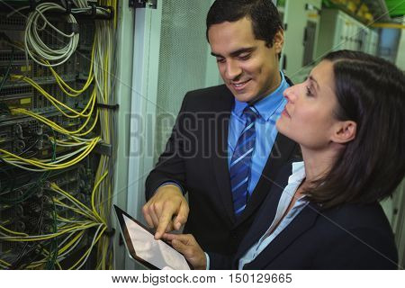 Technicians using digital tablet while analyzing server in server room