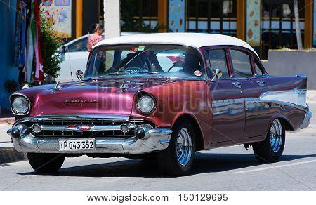 Varadero, Cuba - September 11, 2016:  Red American Classic Car Dirves in Varadero City, Cuba