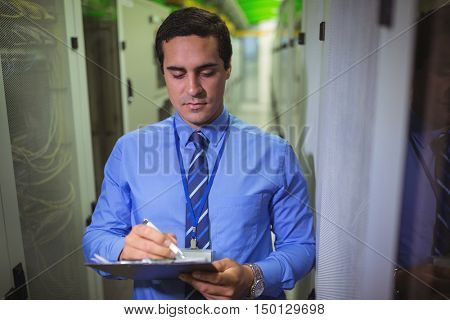 Technician maintaining record of rack mounted server on clipboard in server room