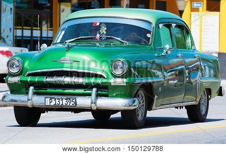 Varadero, Cuba - September 11, 2016:  green American Classic Car Dirves in Varadero City, Cuba