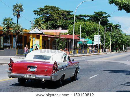 Varadero, Cuba - September 11, 2016:  Red and white American Cabriolet Classic Car Dirves in Varadero City, Cuba