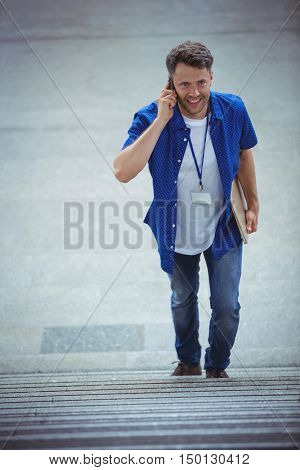 Handsome man walking on stairs while talking on mobile phone at railway station