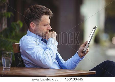 Businessman using digital tablet at outdoor caf\xED\xA9