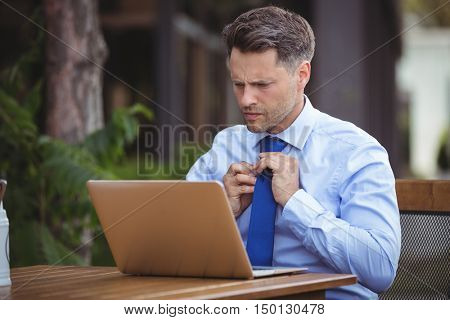 Handsome businessman adjusting tie while using laptop at outdoor