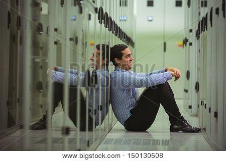 Happy technician sitting on floor in server room