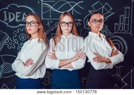 Two Europeans and Asian business women with glasses standing on a dark background pattern