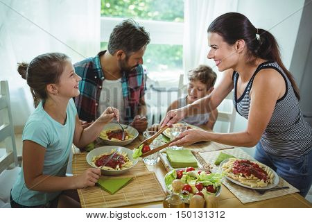 Smiling woman serving meal to her family at home