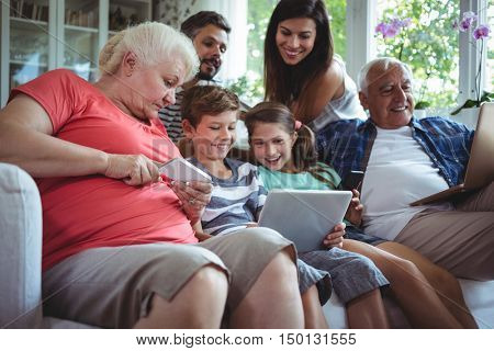 Happy multi-generation family sitting on sofa and using laptop, mobile phone and digital tablet