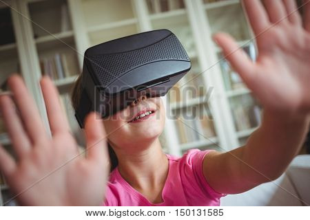 Girl looking through virtual reality headset in living room at home
