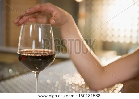 Woman having red wine at bar counter in bar