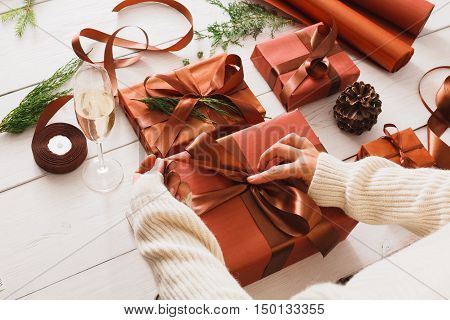 Gift wrapping background. Female hands packaging stylish christmas present boxes in maroon paper decorated with satin ribbon bows. Christmas and winter holidays concept. Still life