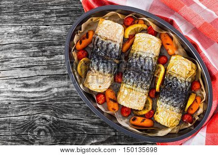 rolls-up of fillet of mackerel with grilled carrots cherry tomatoes and lemon in baking dish with checkered kitchen towel on dark wooden planks view from above