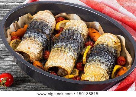 healthy baked fillet of mackerel with carrots cherry tomatoes and lemon in oval baking dish on dark wooden boards with kitchen towel view from above close-up