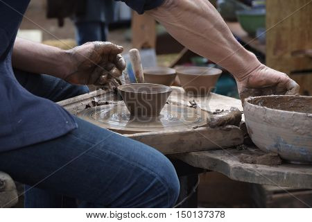 potter creating a new ceramic of clay on the potter's wheel in the pottery selected focus and narrow depth of field