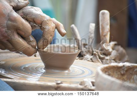 potter's hands creating a new ceramic of clay on the wheel in the pottery closeup with selected focus and narrow depth of field