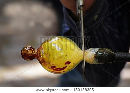 traditional glassblower working on a christmas bauble of melted glass on a rod